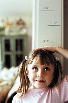 девочка измеряет свой рост