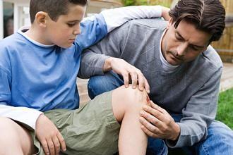 Папа осматривает больную коленку у сына
