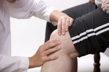 врач осматривает больное колено