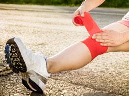 спортсмен бинтует колено