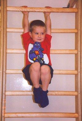 мальчик висит на гимнастической стенке
