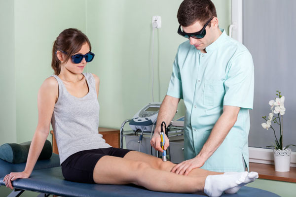 ортопед выполняет процедуру лазерного лечения колена у пациента