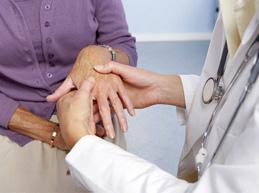 врач осматривает суставы кисти пациента