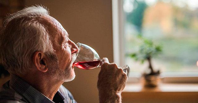 пожилой мужчина пьет вино